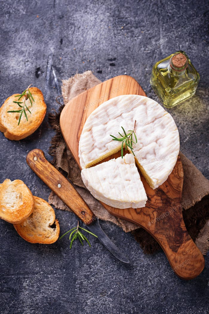 Camembert cheese with rosemary on wooden board