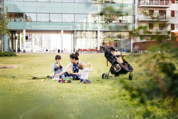 Mother with sons (2-3, 4-5) sitting on grass