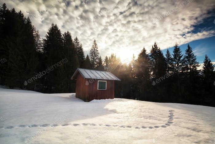 morning sunrise over cabin in winter alpine forest