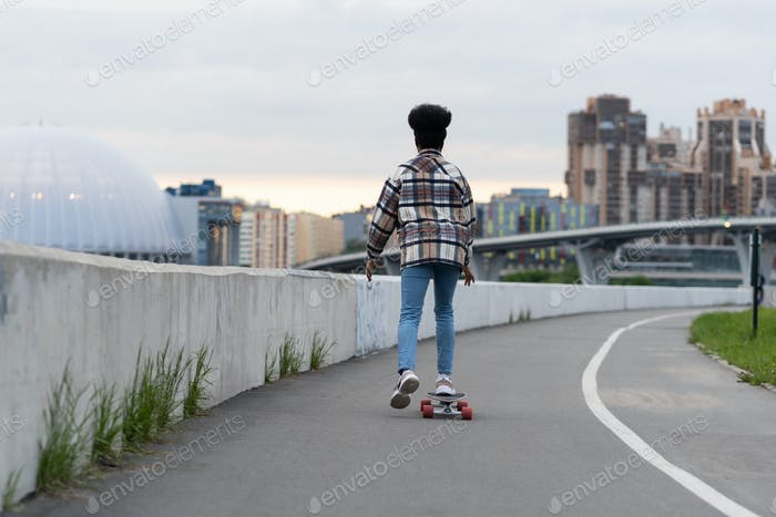 African skateboarder girl riding londboard over cityscape. Female with afro hairstyle on skateboard