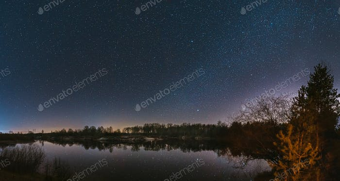 Belarus, Eastern Europe. Night Sky Stars Above Countryside Landscape With River. Natural Starry Sky