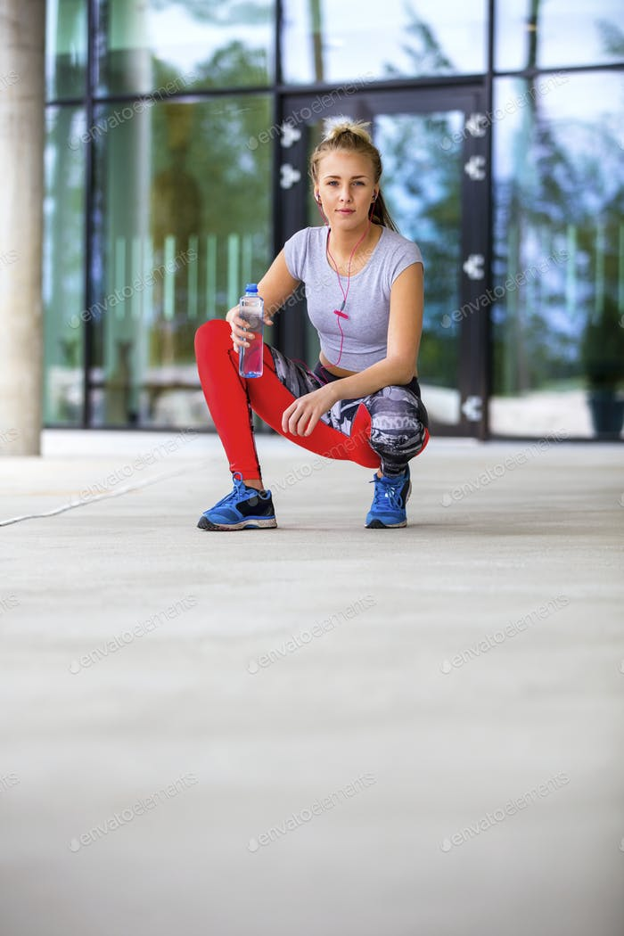 Sporty Woman Holding Water Bottle While Crouching On Footpath