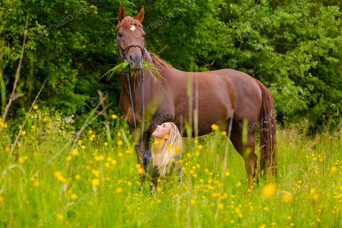 Smiling woman sitting in the meadow and communicate with her arabian horse