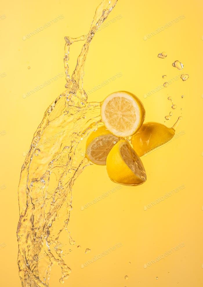 Lemon halves splashing in mid air against yellow background
