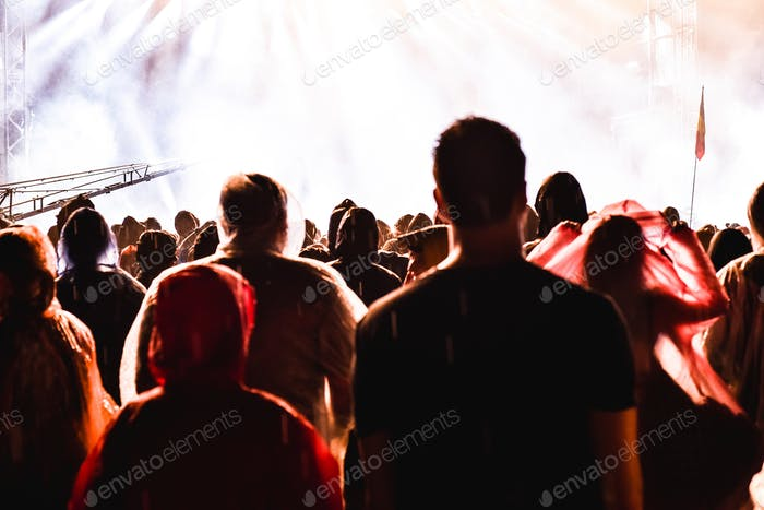 Cheering crowd of people in front of bright stage lights. Music concert