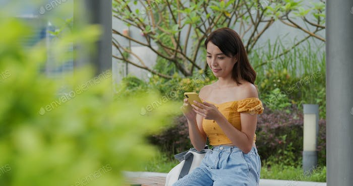 Young woman play on cellphone at outdoor