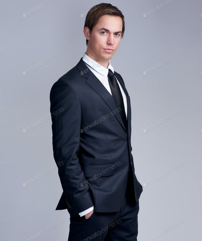 Handsome young businessman standing against gray background