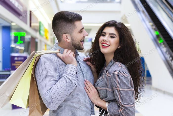 Happy couple embracing and posing after shopping