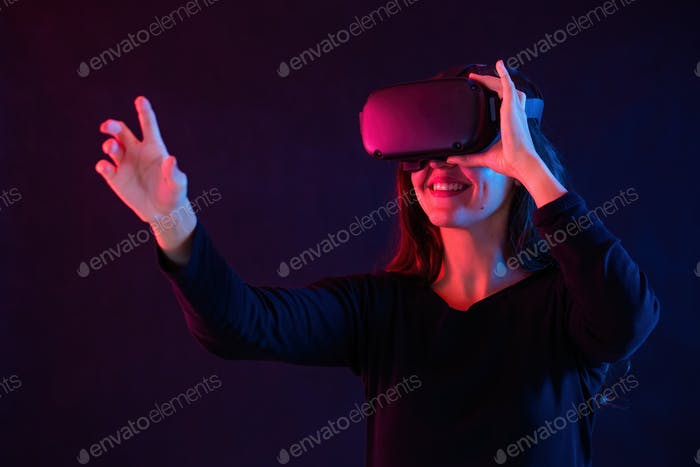 Smiling woman with headset interacting in virtual reality