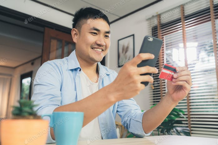 Asian man using smartphone for online shopping and credit card in internet at living room home.