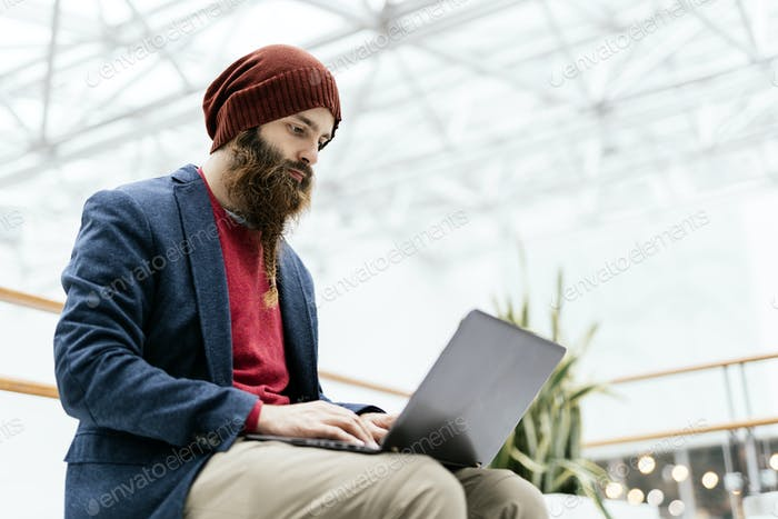 Hipster man using laptop indoors