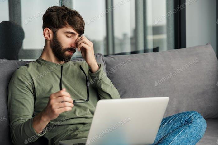 Bild von müde bärtigen Mann hält Brillen und arbeiten mit Laptop