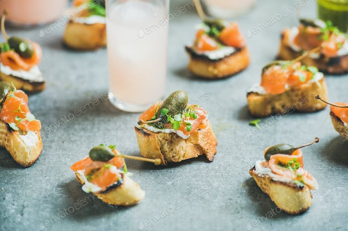 Crostini with smoked salmon and pink grapefruit cocktails, grey background
