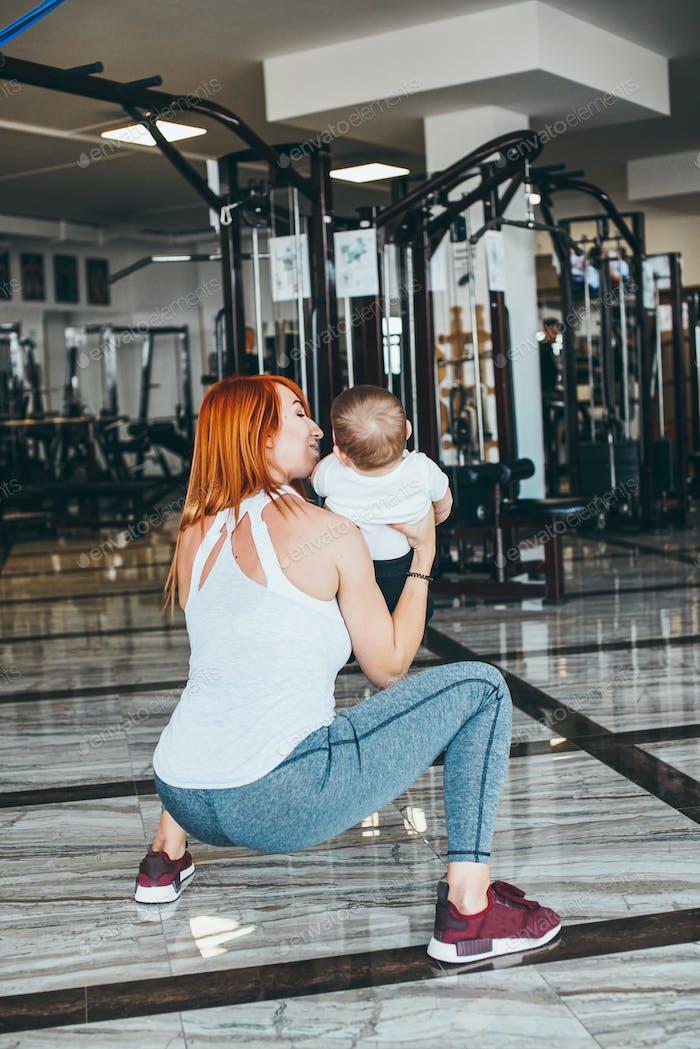 joven madre con su hijo joven en el gimnasio
