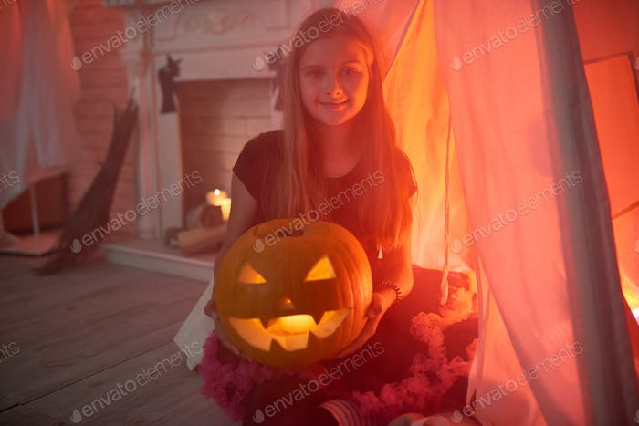 Little Girl Holding Carved Pumpkin