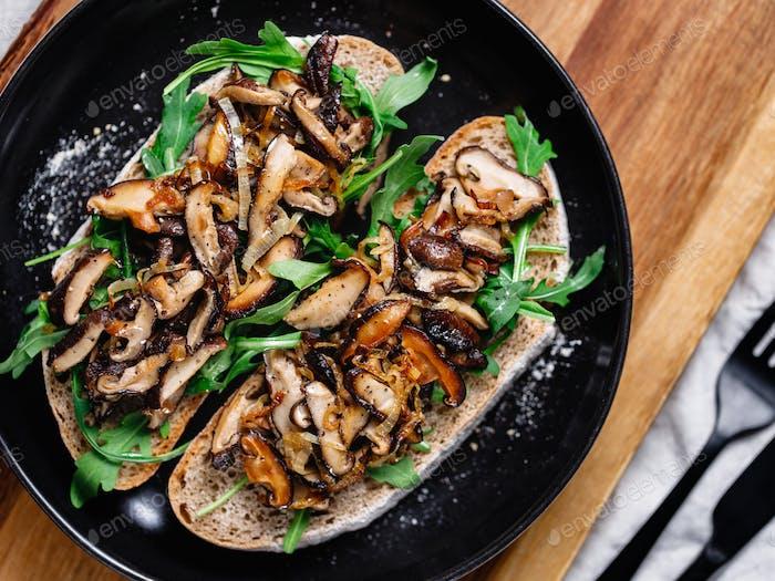 Top view of two vegan sandwiches with fresh arugula, fried shiitake mushroom and shallot onion.