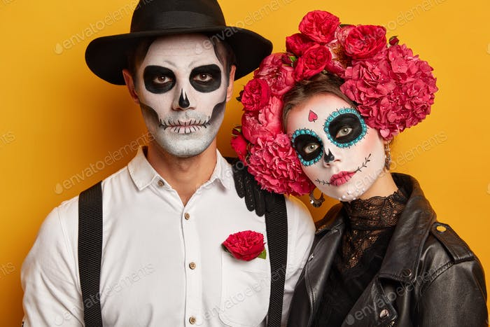 Couple have painted faces, take part in zombie walk, commemorate dead during Day of Death in Mexico,