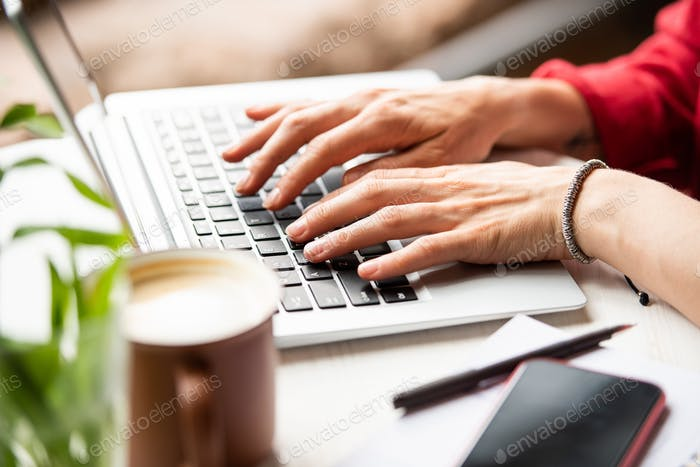 Hands of young businesswoman on laptop keypad surfing in the net