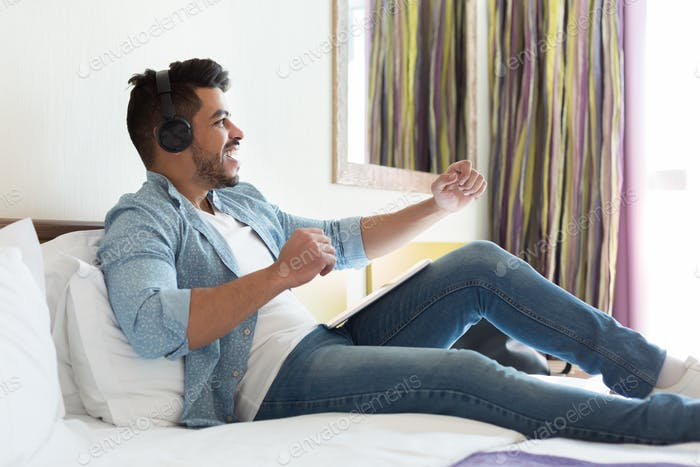 Handsome young man in headphones listening to music on tablet