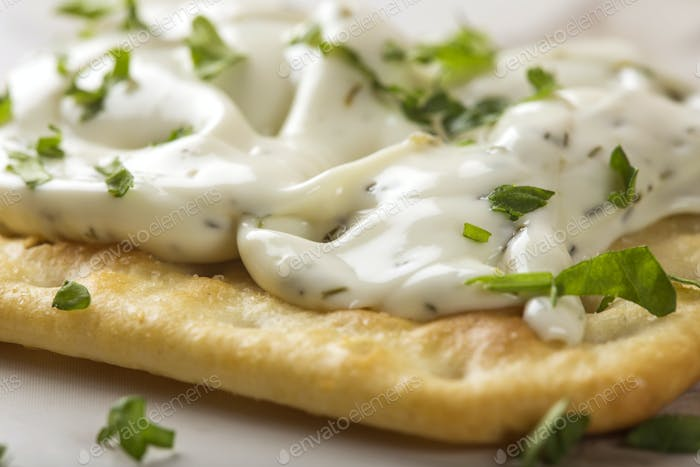 one thin crispy crackers with cream cheese and parsley