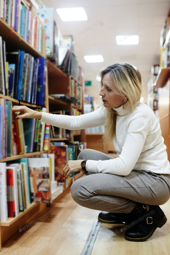 Young female making order on bookshelves in college, teacher picking literature for education