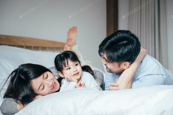 Happy family playing together in bedroom