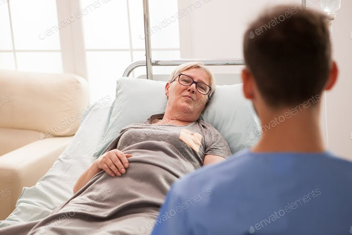 Old female laying on bed in a nursing home talking with male doctor