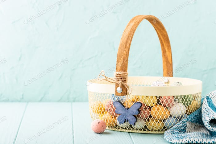 Metal basket with colourful Easter quail eggs
