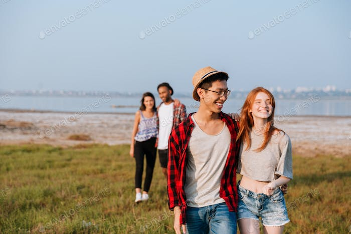 Two cheerful couples hugging and walking outdoors