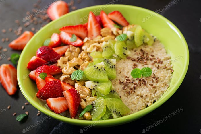 Tasty and healthy oatmeal porridge with berry, nuts and flax seeds.