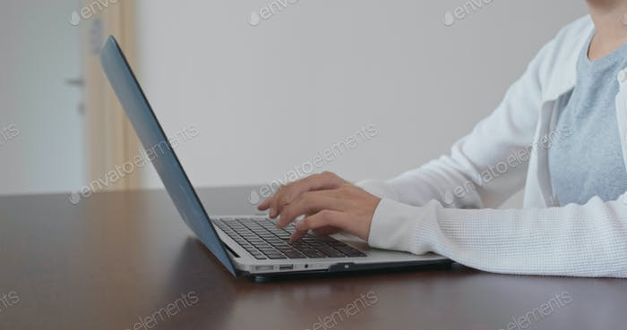 Woman type on computer at home