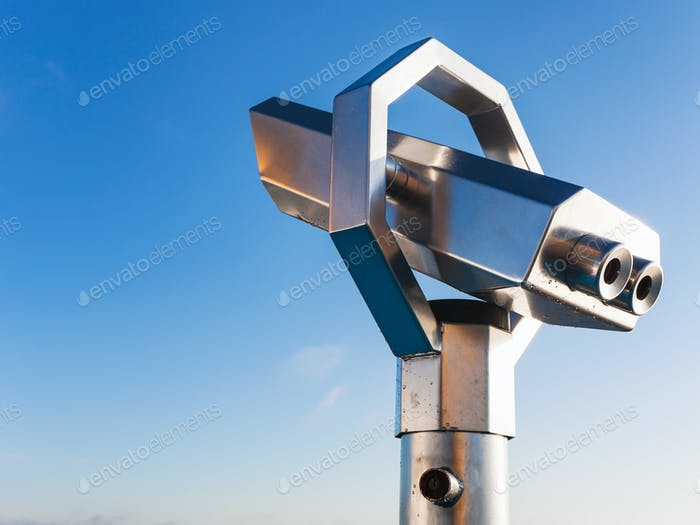 stationary observation binoculars and blue sky