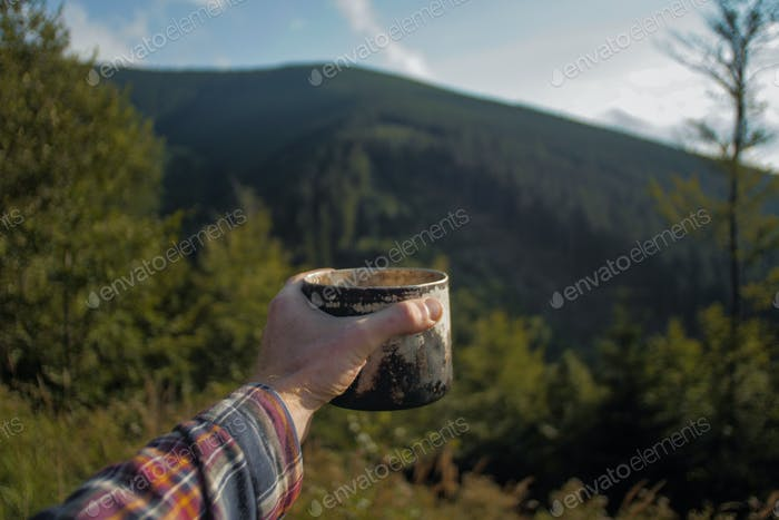 point of a view, mans hand holding a cup of coffee outdoors on a hiking trip
