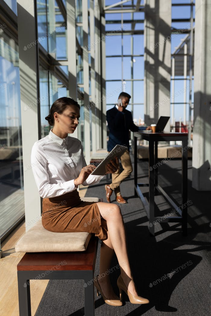 Pretty young Caucasian businesswoman using digital tablet while sitting on bench.