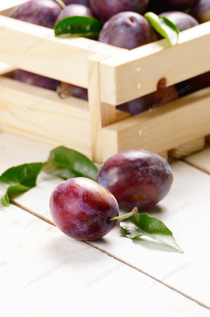 Wooden crate with plums closeup