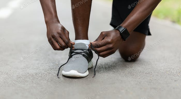 Closeup of african guy fixing his sport shoes