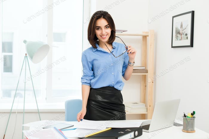 Brunette girl in blue shirt and black skirt is standing near table in office. She holds glasses in