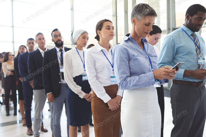 Front view of diverse business people waiting in queue in lobby at office
