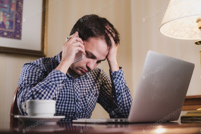 tired man with laptop and coffee having a work call on his phone, businessman in office or home