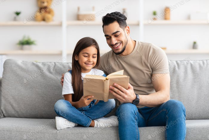 Father and daughter reading book spending time together at home
