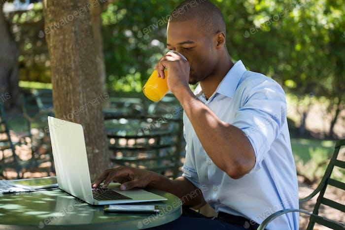 Man drinking juice while using laptop at restaurant