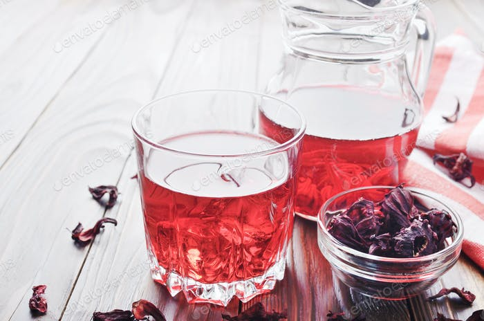 Closeup view at glass of hibiscus ice tea and jug on wooden tabl
