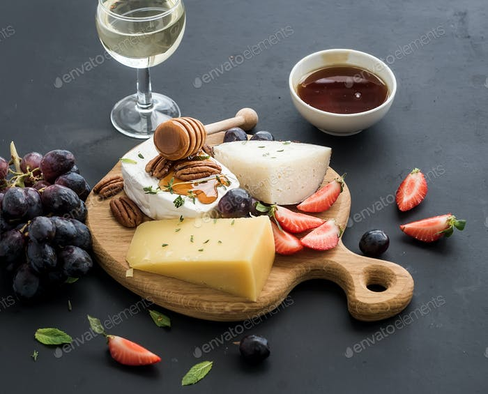 Cheese appetizer selection or whine snack set. Variety of cheese, grapes, pecan nuts, strawberry