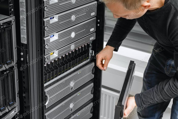 Male IT Consultant Examining SAN At Datacenter