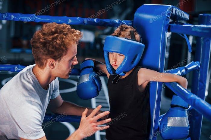Молодой тренер по боксу помогает маленькому мальчику в защитной одежде на ринге между раундами