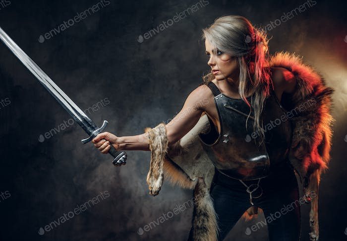 Portrait of a beautiful warrior woman holding a sword wearing steel cuirass and fur. Fantasy fashion