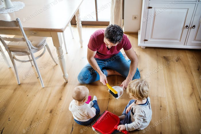 Father and two toddlers with brush and dustpan.