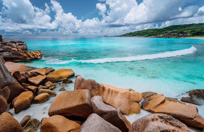 Rolling wave and stunning granite formations on the beautiful tropical island with white clouds of
