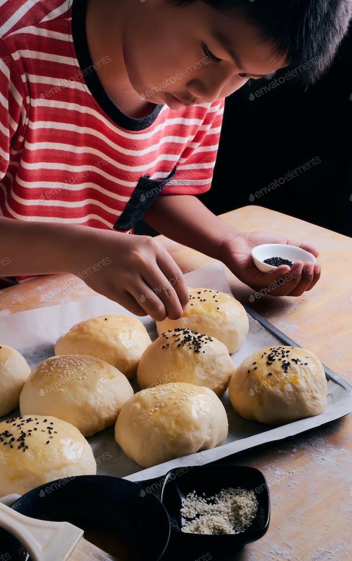 A boy sprinkle the sesame seeds on the dough of buns