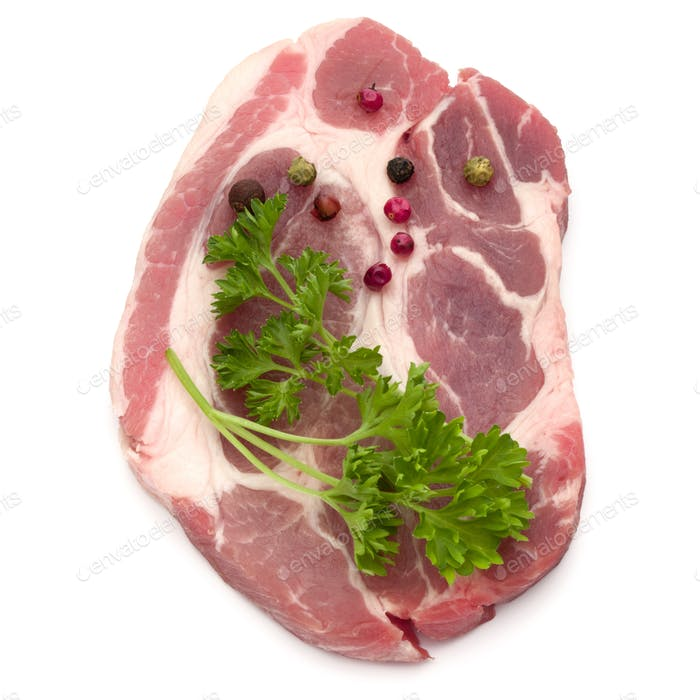 Raw pork neck chop meat with parsley herb leaves and peppercorn spices garnish isolated on white